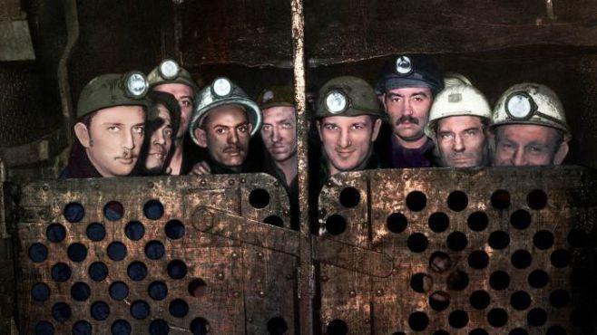 Groupe de mineurs, dans l'ascenseur, à la remontée de la fosse